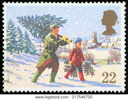 UNITED KINGDOM - CIRCA 1990: A stamp printed in the United Kingdom shows Man Carry Christmas Tree, circa 1990.