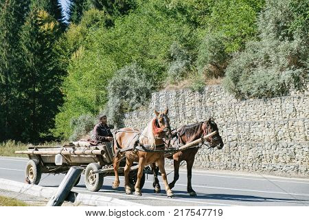 Targu Mures, Romania - September 28, 2017: Man driving a horse-drawn cart in a suburb of Targu Mures, Romania. Horse cart on Romanian roads is a kind of landmark.