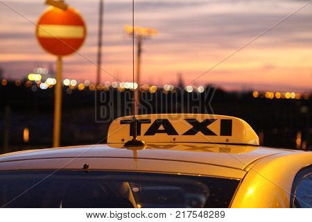 Taxi waits under streetlight at sunset with city in background