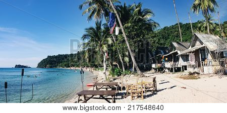Koh Chang, Thailand - December 18, 2015: View of the Lonely Beach with tropical vintage cafe Chang island, Thailand. Unidentified tourists enjoying their holidays on Thai beach at hot summer day