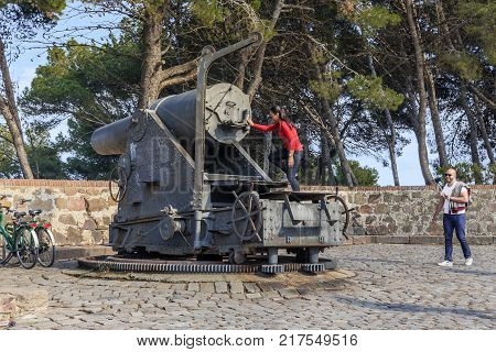 BARCELONA, SPAIN - MAY 11, 2017: Unidentified tourists are preparing for a photo shoot on the artillery gun of the coastal battery near the castle of Montjuic.