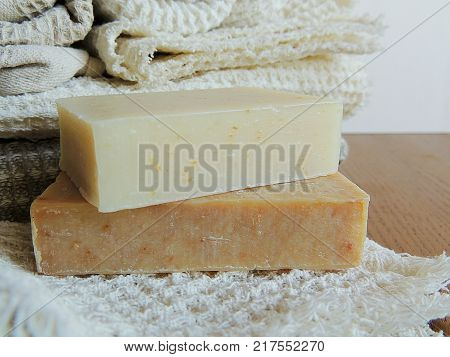 Handmade spa bath soap on white handmade linen waffle texture wash cloth, towel, wooden background. Soap making. Soap bars. Spa, skin care.