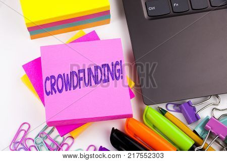 Writing text showing Crowdfunding made in the office with surroundings such as laptop, marker, pen. Business concept for Business Fundraising Project Funding Workshop white background space