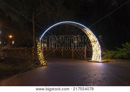 Gdansk, Poland - December 8, 2017: Illuminated gate as winter christmas illumination at night in Oliwa park in Gdansk.