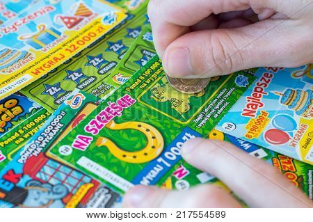 Pruszcz Gdanski, Poland - December 1, 2017: Man hand scratching a Polish Lotto lottery scratch card with coin.
