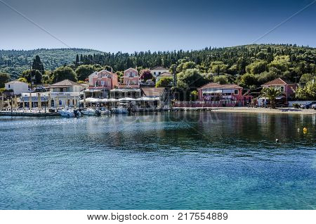 boats moored in the port and elegant villa of fiskardo and also bay of the same name north of the island of Kefalonia