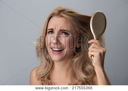 Haircare concept. Portrait of disappointed middle-aged woman is being not able to comb her curls. She is making efforts while pulling her hair and frowning her face while feeling pain. Isolated