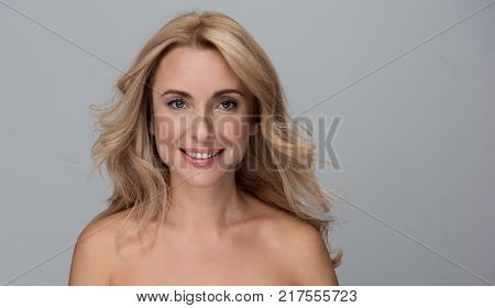 Beauty concept. Portrait of happy attractive middle-aged woman is standing with naked shoulders and looking at camera with wide smile. Isolated background with copy space in the right side