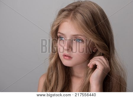 Serious lovely little girl is looking aside wistfully. She is standing and touching her hair. Isolated background with copy space in the left side