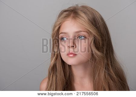 Feeling lonely. Serious little girl is standing and looking aside wistfully. Isolated background