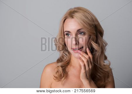 Portrait of delighted charming middle-aged naked woman is touching her lips and opening mouth while looking aside wistfully. Isolated background with copy space in the left side