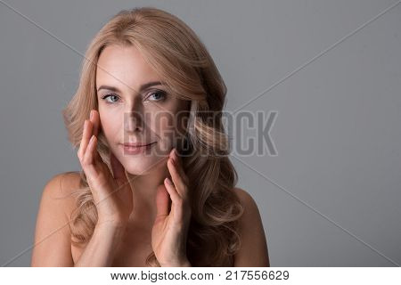 Natural attractiveness. Portrait of charming naked middle-aged woman is touching her face while standing and looking at camera temptingly. Isolated background. Copy space