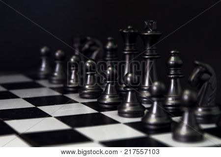 Black chess figures on board. Black chess set in order for game start. Black chess figures row on checkered board. Chess figurine order. Checkmate game banner template. Intellectual sport. Tactic game