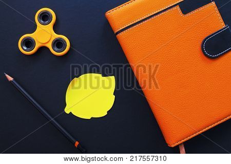 Orange notebook and spinner flat lay photo on black background. Spinner and sticker note. Autumn season flat lay with draw tools. Hipster table with blank sticker. Yellow leaf sticker with text place