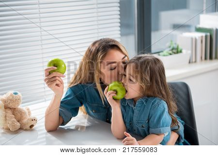 I love you. Affectionate mother is kissing girl while hugging the child. Kid is eating an apple with appetite
