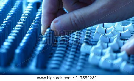Sound technician hands working on audio mixer faders and knobs. Music production and sound engineering background. Shallow depth of field.