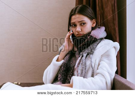 sad young girl got sick with angina because of cold weather, talking on the phone