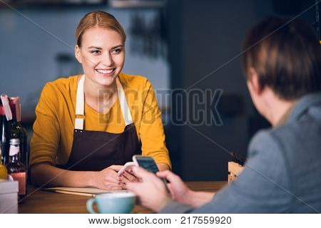 Portrait of cheerful female barista giving phone number to client while having job in confectionary shop. Acquaintance concept