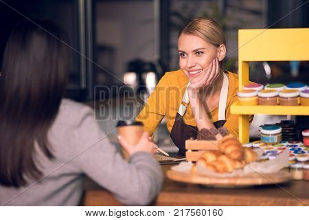 Portrait of cheerful young female barista speaking with visitor at table. She tasting cup of coffee. Communication concept