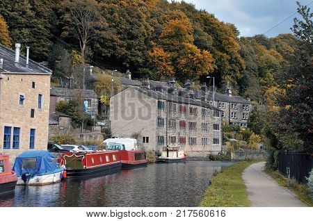 hebden bridge with barges and houseboats on the rochdale canal with old stone houses and surrounding woodland in autumn