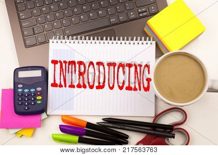 Word writing Introducing in the office with  laptop, marker, pen, stationery, coffee. Business concept for Introduction Start Intro Beginning Workshop white background with space