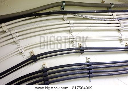 Electric tubes on the white wall in the building