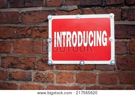Hand writing text caption inspiration showing Introducing concept meaning Introduction Start Intro Beginning written on old announcement road sign with background and space