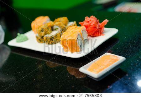 Philadelphia roll classic dark stone on the Board. Salmon, Philadelphia cheese, cucumber, avocado. Japanese sushi