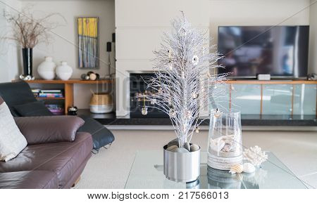Simple summer Christmas small white tree on glass table with seaside vase decoration in lounge.