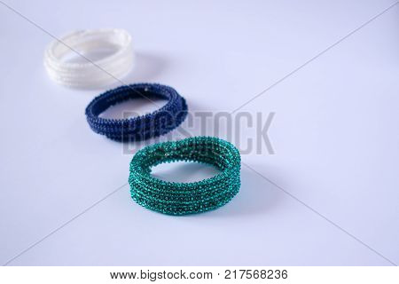Three bracelets lie on a light background. Bracelets of different colors