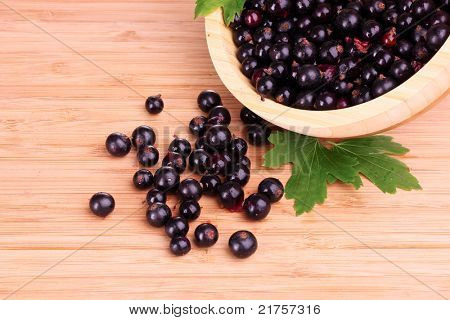 fresh blackcurrant in bowl on wooden surface