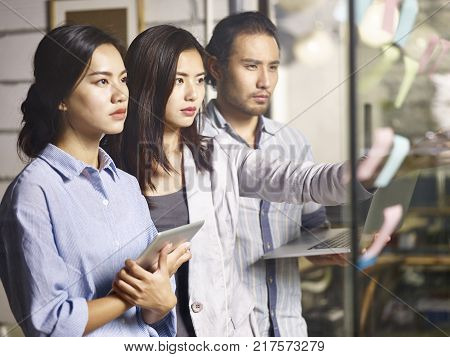 three young asian entrepreneurs teaming up analyzing business situation using laptop computer digital tablet and adhesive notes in office looking serious and pressured.