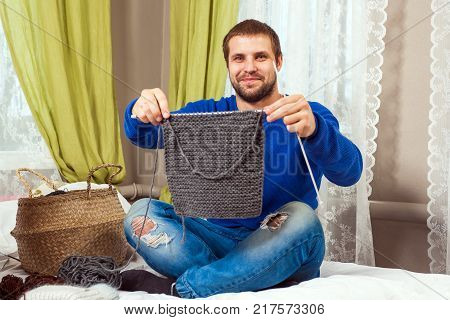 A young dark haired man in a blue sweater and jeans shows how he tied a piece of a gray sweater with knitting needles from natural strings and sits on a bed in a home setting