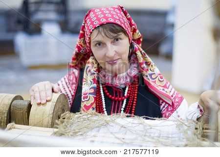 Belarus Gomel September 15 2017. The city's birthday. A Belarusian woman is weaving a towel. Take up weaving. Spin the towel.