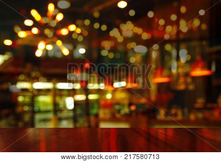 top of wood table with Christmas party bar or pub at night with light lamp background