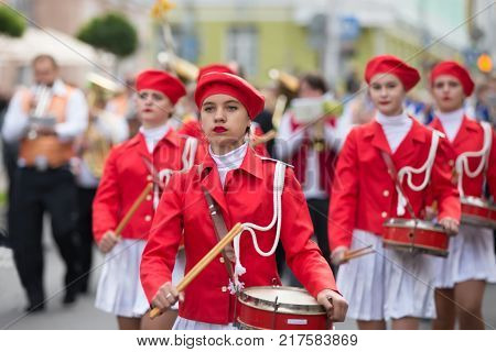 Belarus Gomel September 16 2017. Celebrating the city day.The drum orchestra is walking along the street. Young female drummer in red clothes with a drum. Street drummer.