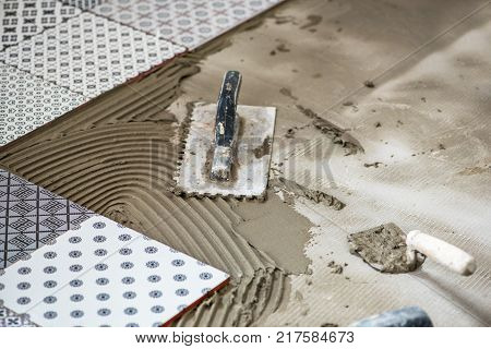 Professional worker gluing decorative tile on wall.