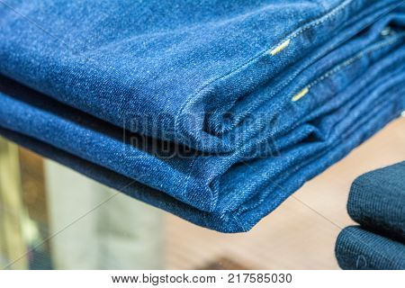 Jeans stacked on a wooden background in shopping moll