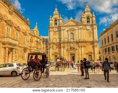 Mdina Malta October 7 2017: picturesque horse carriage and tourists on catholic St. Peter & Paul Cathedral
