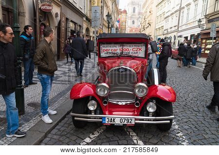 PRAGUE - DECEMBER 29 2016: Vintage red car waiting for tourists for a guided city tour