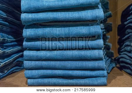 Jeans stacked on a wooden background  on market