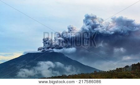 Mount Agung erupting plume. During volcano eruption thousands of people was evacuated from dangerous zone. Airline flights to Bali were canceled Denpasar airport closed because of volcanic ash clouds