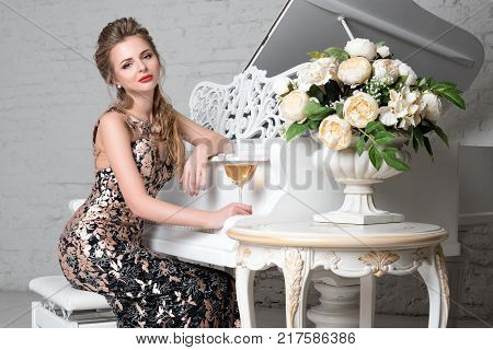 Elegant blonde lady with glass of wine in restaurant sitting near white grand piano in a luxury classic interior. Beautiful sexy young woman with perfect body and pretty face make up wearing evening dress drinking alcohol in luxury interior