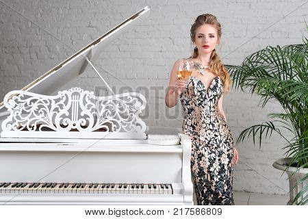 Elegant blonde lady with glass of wine in restaurant standing near white grand piano in a luxury classic interior. Beautiful sexy young woman with perfect body and pretty face make -up wearing evening dress drinking alcohol in luxury interior
