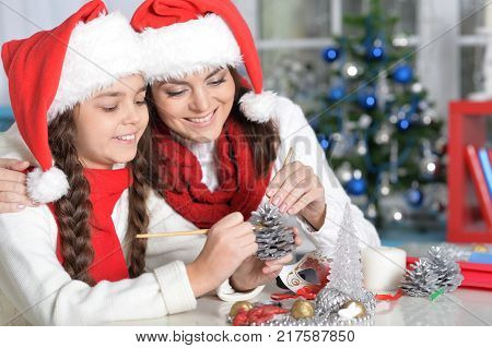 Portrait of ypung mother and her daughter making  Christmas decorations sitting at the table