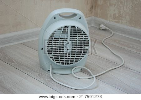 A compact electric heater with a fan on the floor in the room.