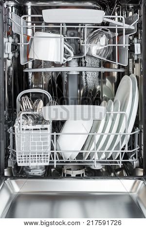 open dishwasher front view. Clean plates, cups, glasses and cutlery in the dishwasher after washing