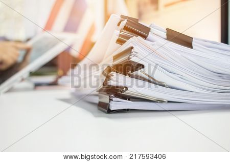 Paper stack Pile of unfinished documents on office desk related to business functions. Stack of business papers for Annual Report files on blur National flaguse tablet. Business offices concept