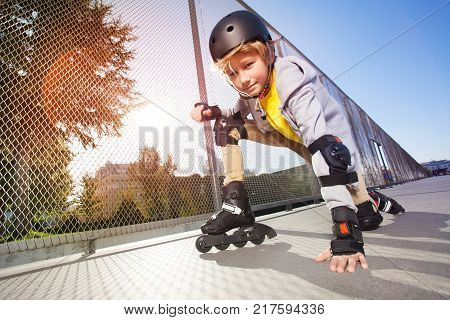 Close-up portrait of preteen boy, roller skater in protective gear, posing on floor at outdoor rollerdrom