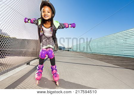 Preteen African girl in roller blades and protective gear doing tricks at skate park